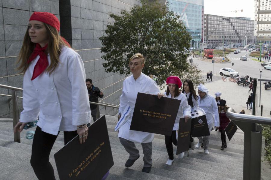 """I perfromers del Frozen Flashmob """"il lavoro nero non ha un buon sapore"""" salgono le scale che li condurranno in Piazza Gae Aulenti"""
